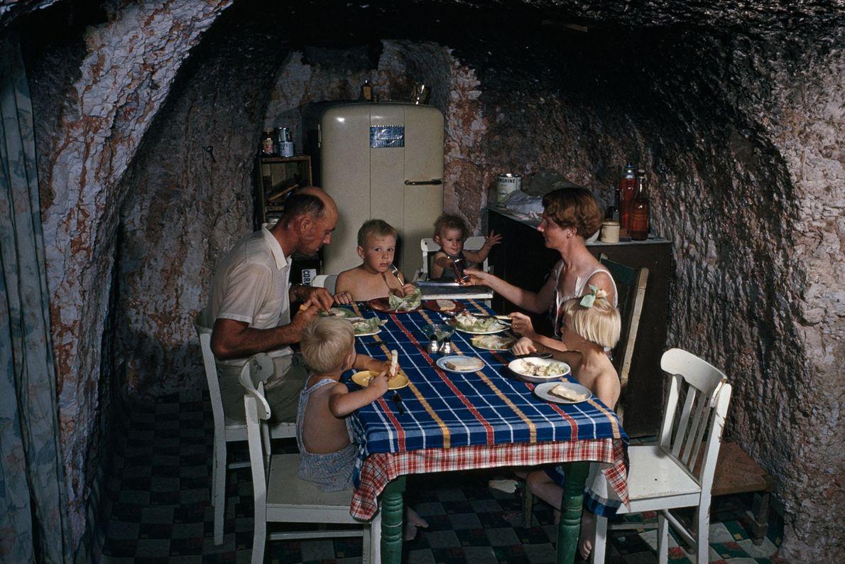 Um mineiro e sua família comem em sua cozinha subterrânea em Coober Pedy, na Austrália.