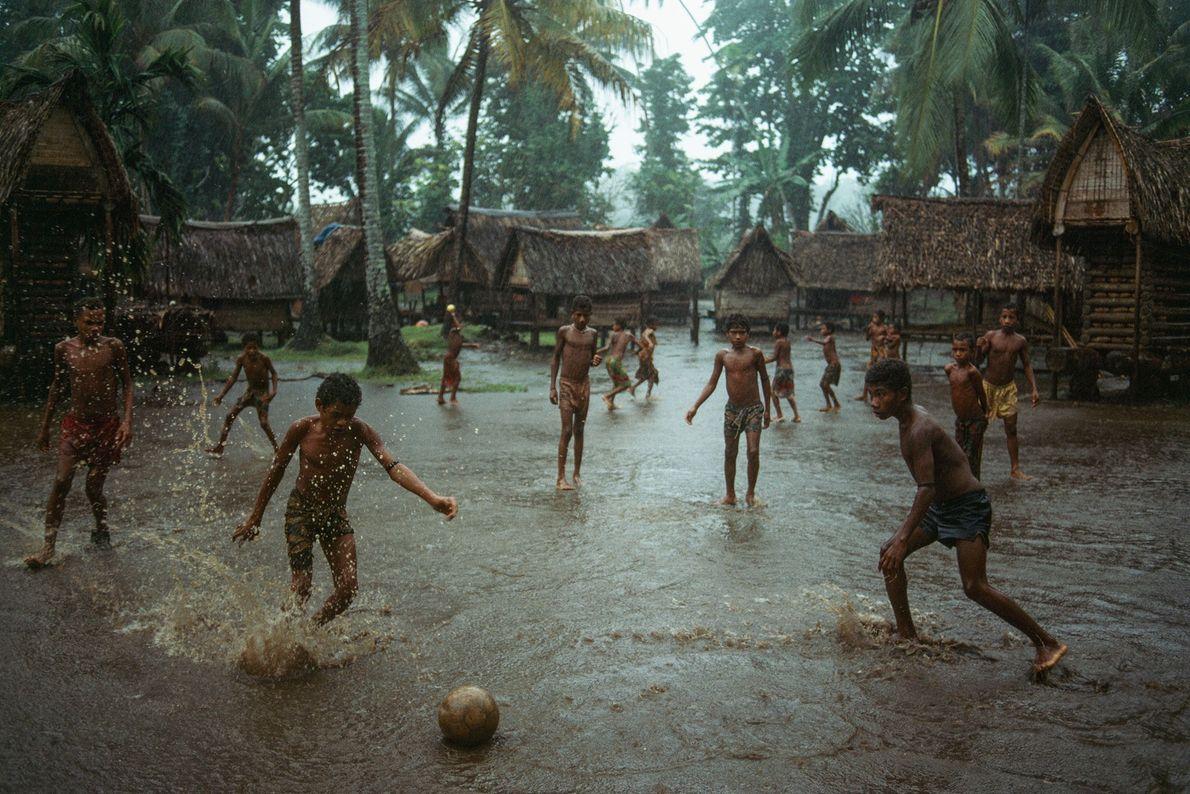 Na Ilha Kiriwina, a maior das Ilhas Tobriand em Papua-Nova Guiné, meninos jogam futebol em uma ...