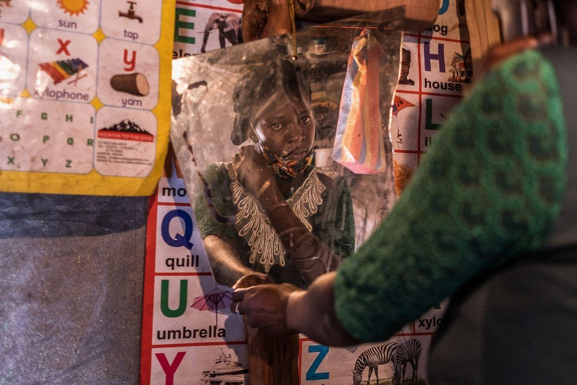 Ruth Kavana, mãe solo de quatro filhos, se olha no espelho dentro de sua casa em ...