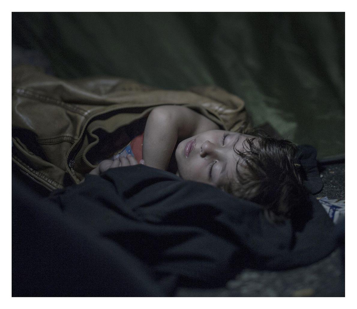 criança refugiada sono na fronteira