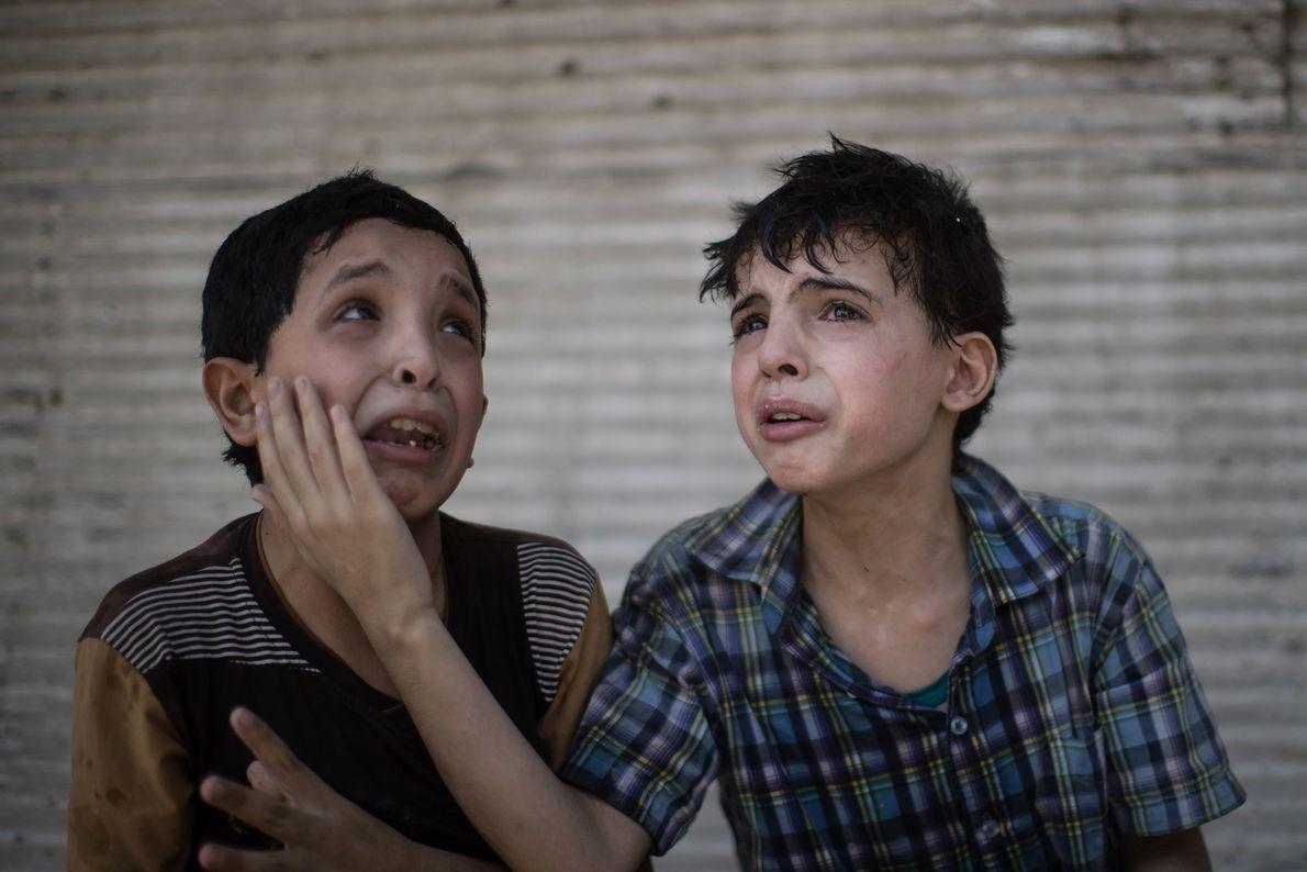 Zeid Ali, 12, à esquerda, e Hodayfa Ali, 11, se consolam ao ver a casa desabada ...