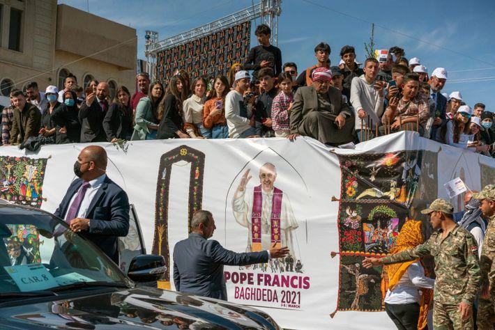 Multidões de cristãos e não cristãos se aglomeram nas ruas de Qaraqosh para ver o comboio ...