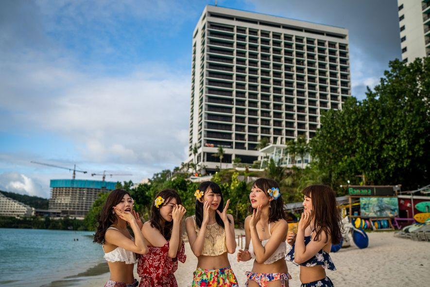 Amigos da Universidade Jin-ai, em Fukui, Japão, fazem pose sob o sol equatoriano em uma praia ...