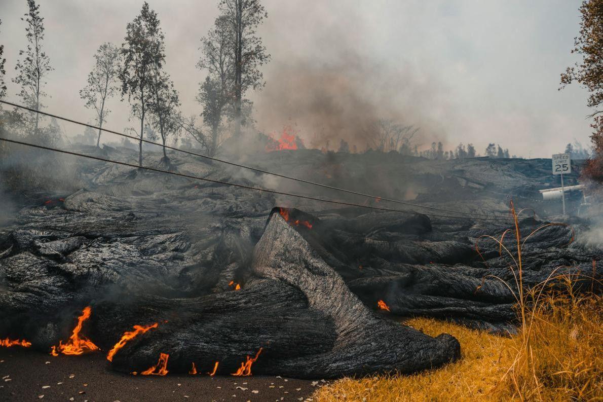 O fluxo de lava Pahoehoe corre morro abaixo a partir de uma fissura ativa, sem poupar ...