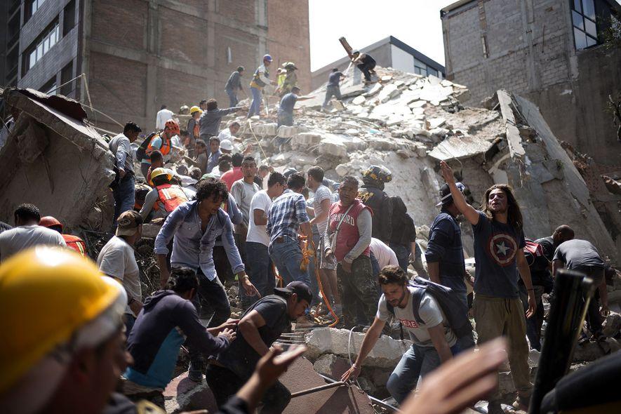 As pessoas removem os destroços de um edifício que colapsou e procuram por possíveis vítimas após …
