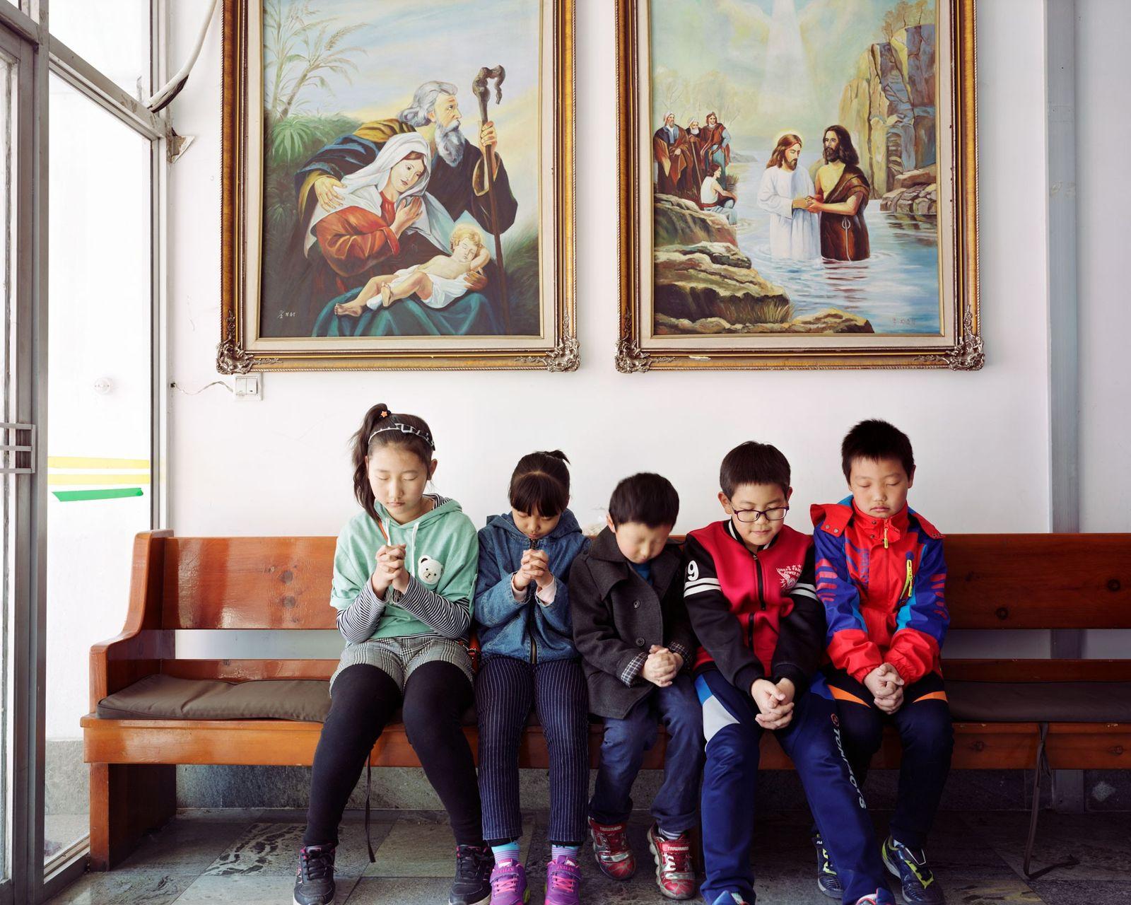 Cinco crianças coreanas rezam em uma igreja local em Longjing, na província de Jilin, na China, ...