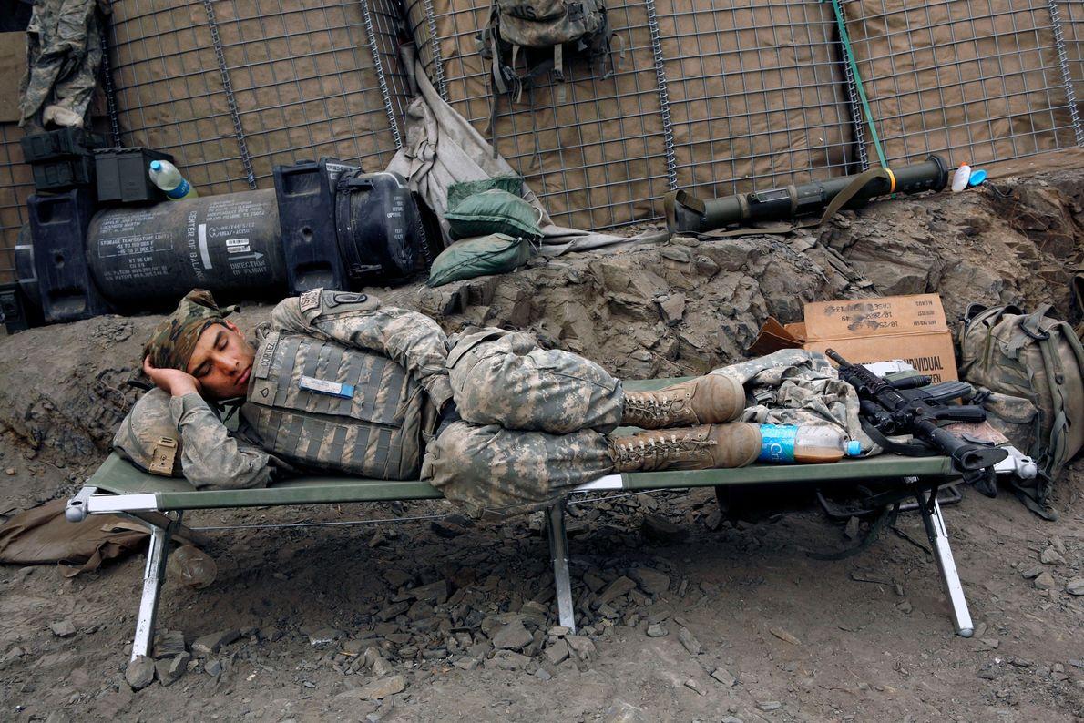 Um soldado americano dorme após o turno da noite em uma base na linha de frente ...