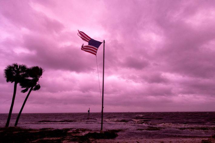 Uma bandeira norte-americana destruída continua a tremular contra o céu rosado do por do sol de ...