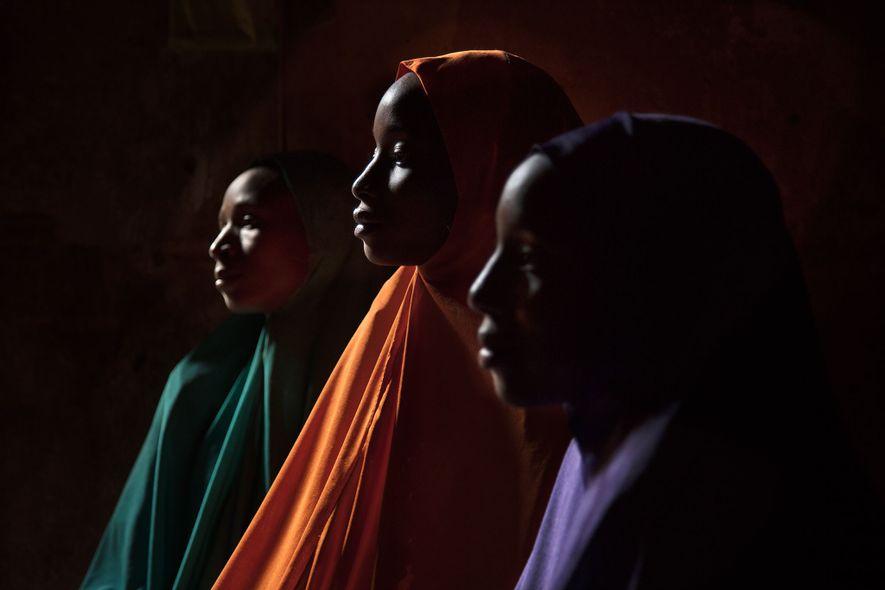 Ya Kaka é retratada aqui com suas irmãs Yagana, 21 (esquerda), e Falimata, 14 (direita). Todas as três foram sequestradas e mantidas em cativeiro pelo Boko Haram. O irmão mais novo e a irmã de Ya Kaka, na época com 6 e 5 anos, respectivamente, também foram sequestrados, mas seu paradeiro permanece desconhecido.