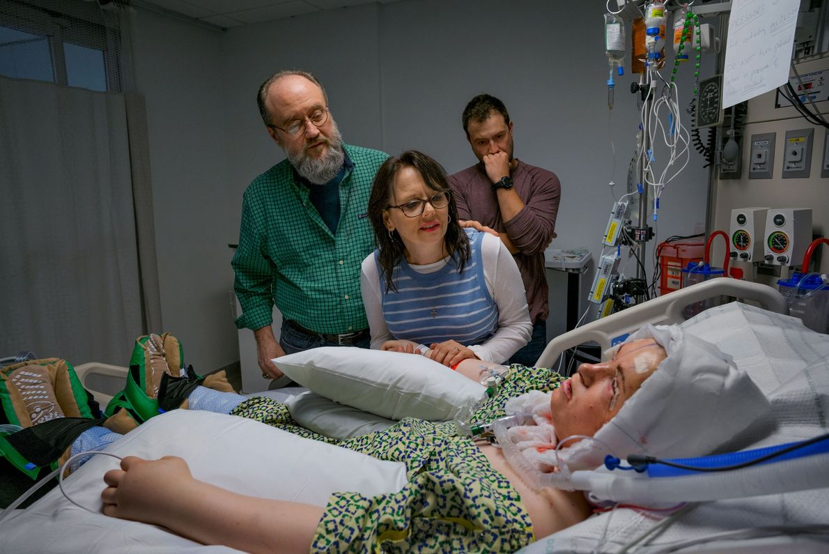 Katie's family looks at her new face after the transplant surgery is complete. During the procedure, ...