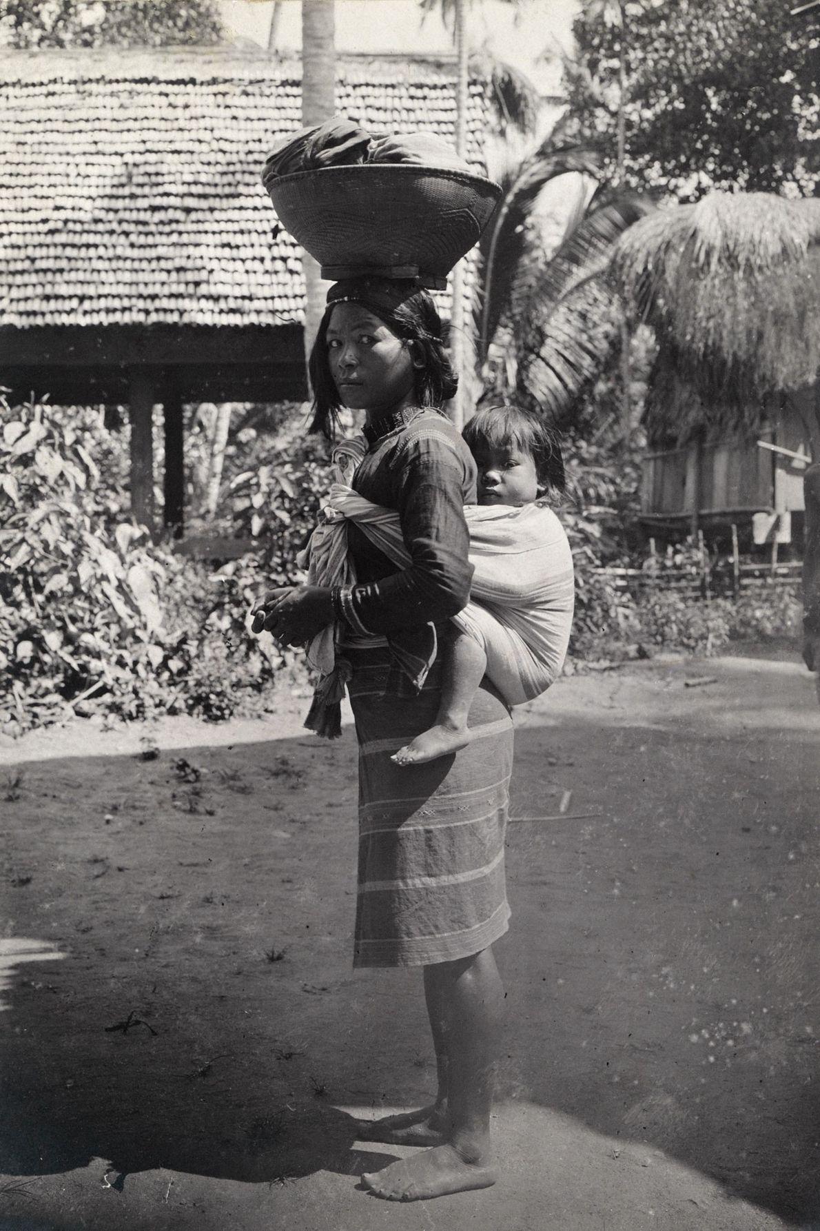 Uma mulher tingian carrega uma criança em suas costas e equilibra uma cesta em sua cabeça ...