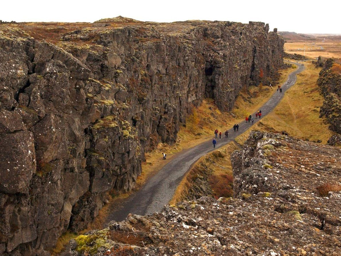 THINGVELLIR - Pessoas caminham na sombra dos penhascos no Parque Nacional Thingvellir, na Islândia. O cume ...