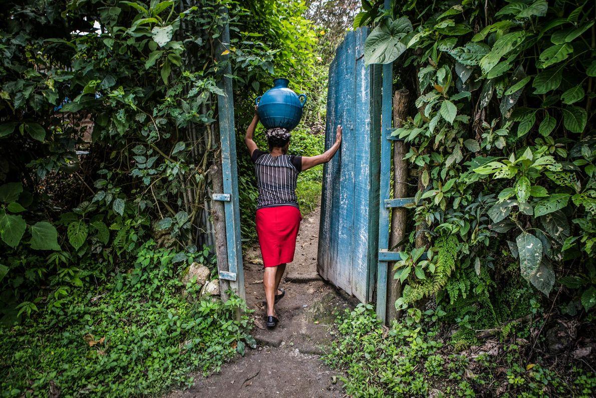 Zoila Ramirez, 40, carrega um jarro de água para sua casa em San Jeronimo Los Planes, ...