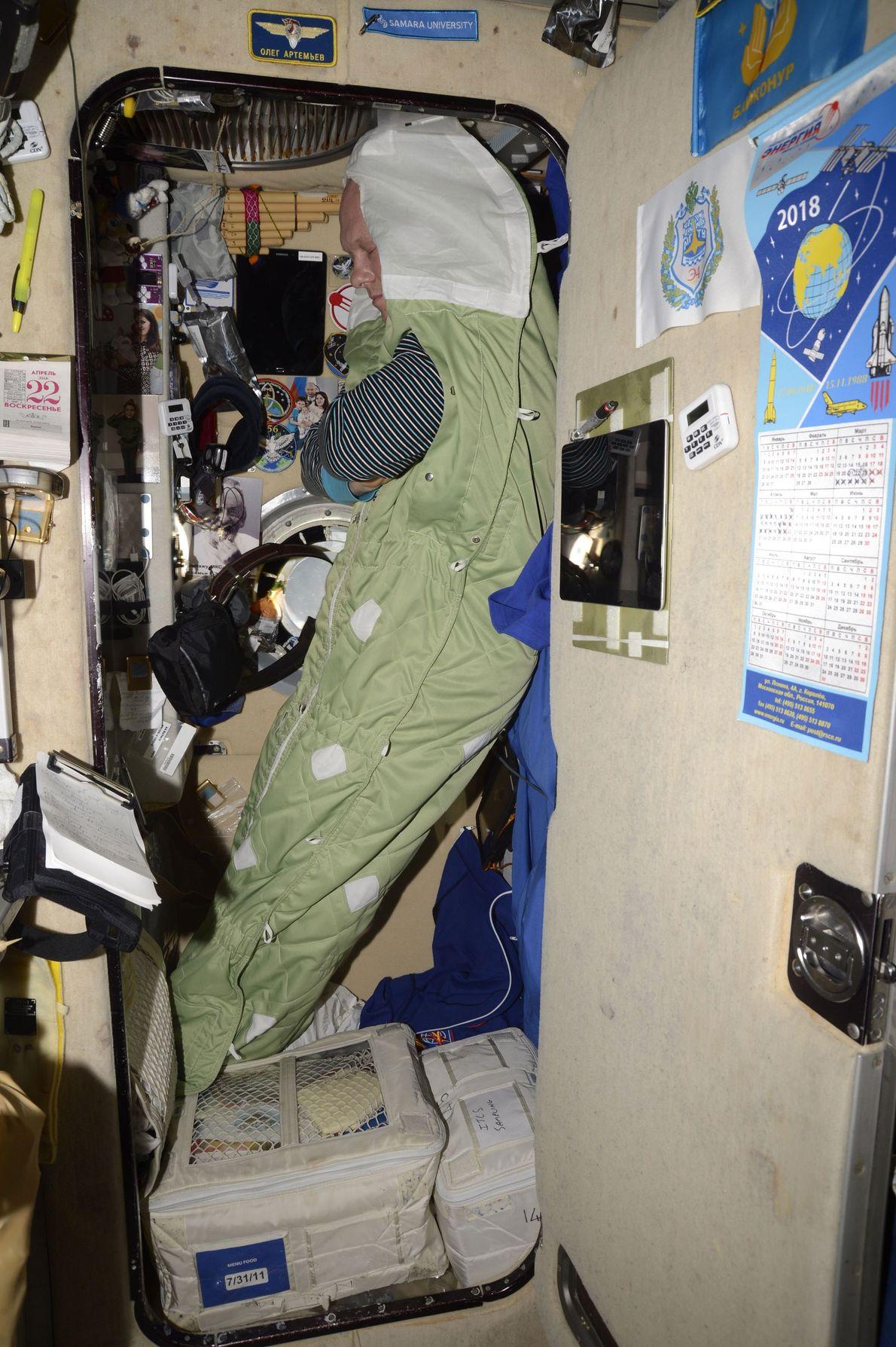 O cosmonauta Oleg Germanovich Artemyev dorme na gravidade zero.