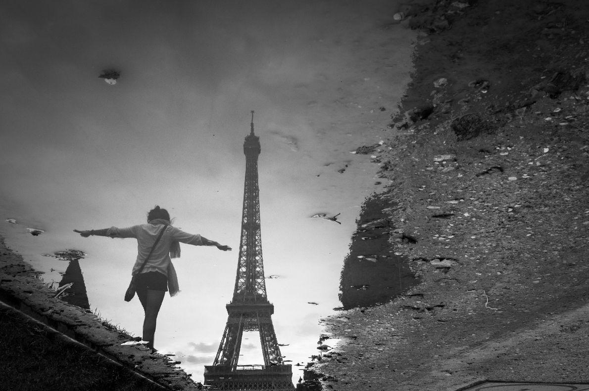 Uma imagem da Torre Eiffel reflete em uma poça no Parc du Champ-de-Mars, que se estende ...