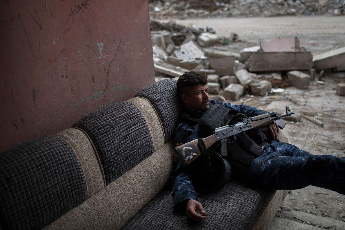 Soldado da Polícia Federal iraquiana senta em sofá antes de ir para a linha de frente ...