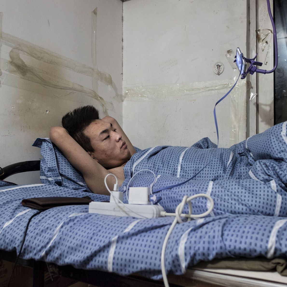 Yi Zhon assiste televisão em seu smartphone deitado na cama, no abrigo atômico de Nong Ying, ...