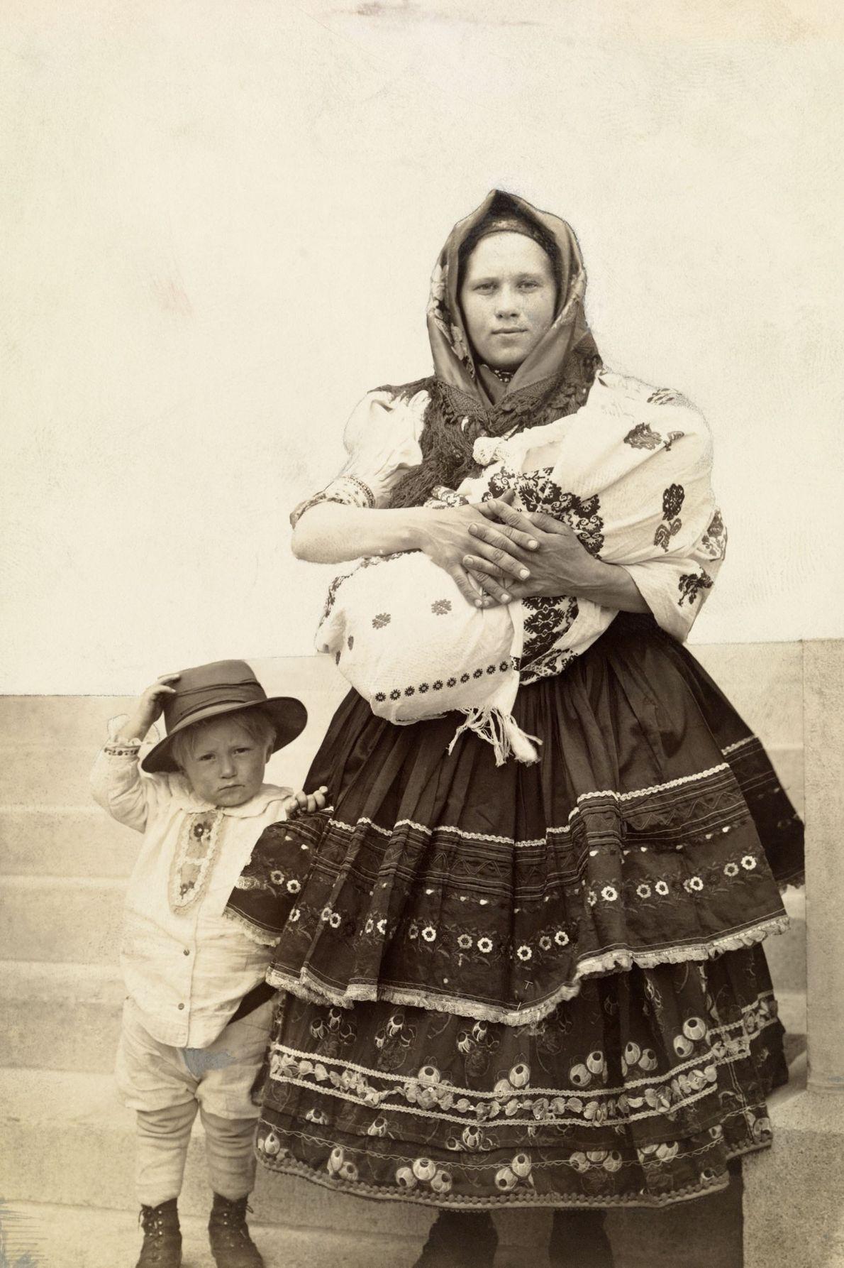 Uma imigrante eslovaca húngara nos Estados Unidos segura seu bebê ao lado de seu filho.