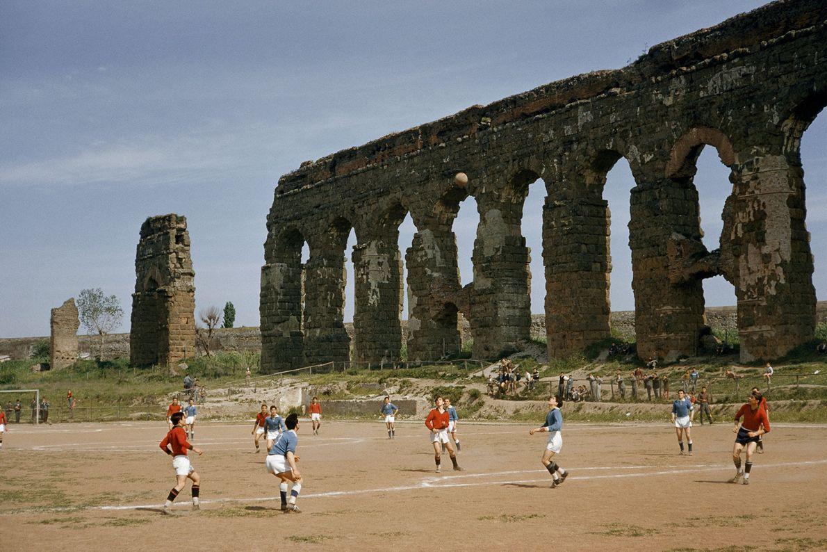 Em 1957, meninos jogam futebol ao lado dos arcos de um antigo aqueduto em Roma, Itália.