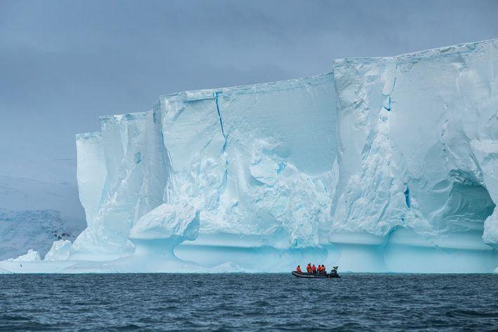 Voltando do trabalho, pesquisadores passam diante de um enorme iceberg que encalhou em frente à estação ...