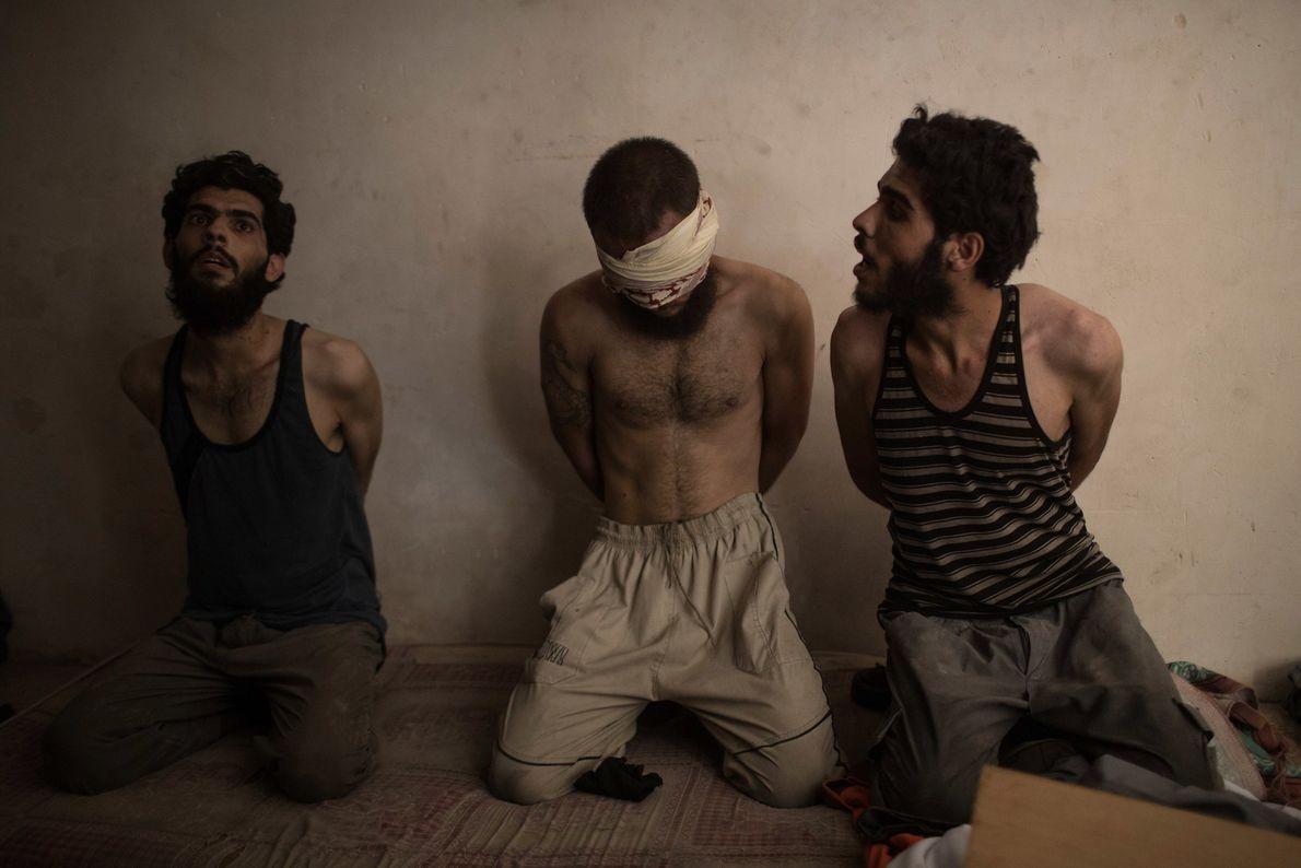 Dois homens são detidos junto com um suspeito militante do Estado Islâmico, no centro, para serem ...
