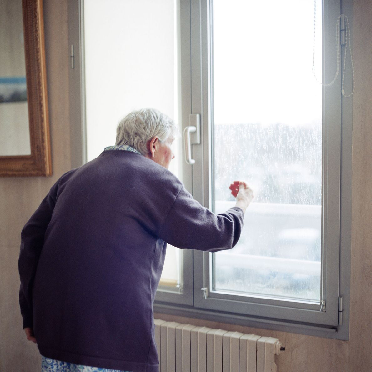 A resident looks out from a sealed window in the ward.