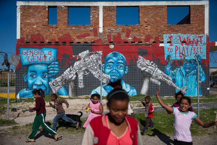 Crianças no bairro de Manenberg, Cidade do Cabo, África do Sul, dominado pelas gangues, brincam em ...