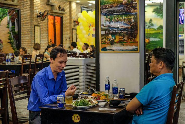 No restaurante Lang Nghe, em Danang, no Vietnã, os clientes jantam sob um cartaz que anuncia ...