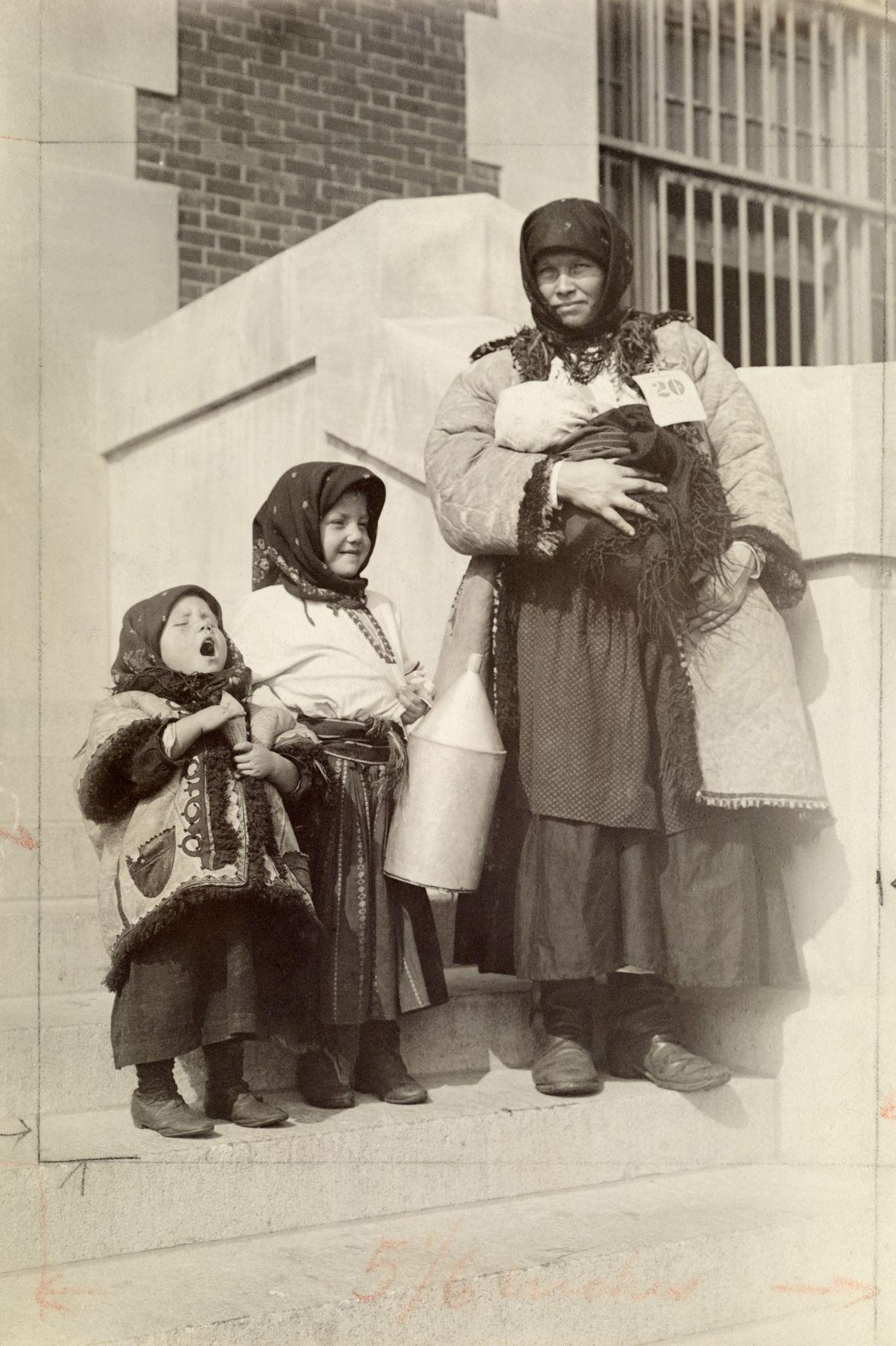 Uma imigrante russa nos Estados Unidos de pé com seus três filhos.