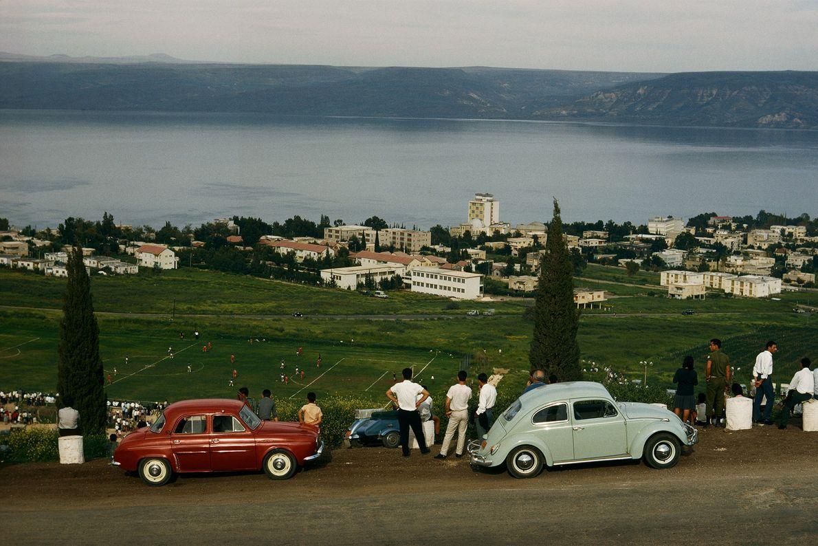 Turistas dirigem seus carros montanha acima e estacionam para assistir a um jogo de futebol em ...