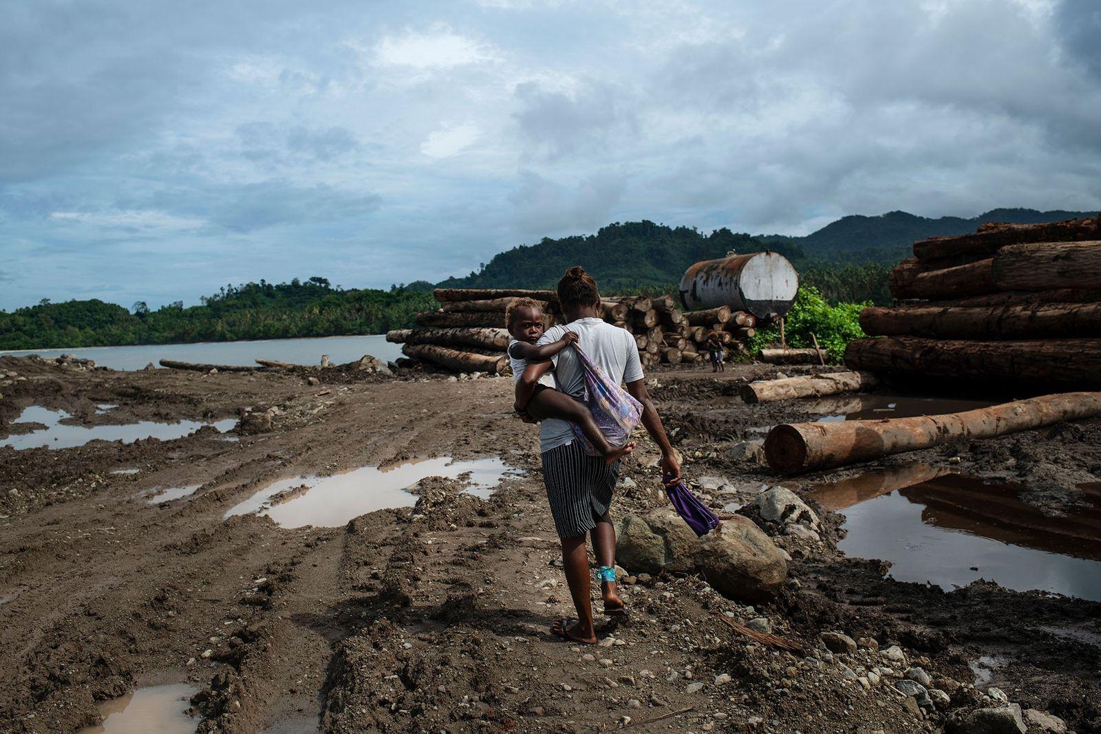 Uma mulher atravessa um ponto de embarque de madeira usado pela empresa Apex, no extremo leste ...