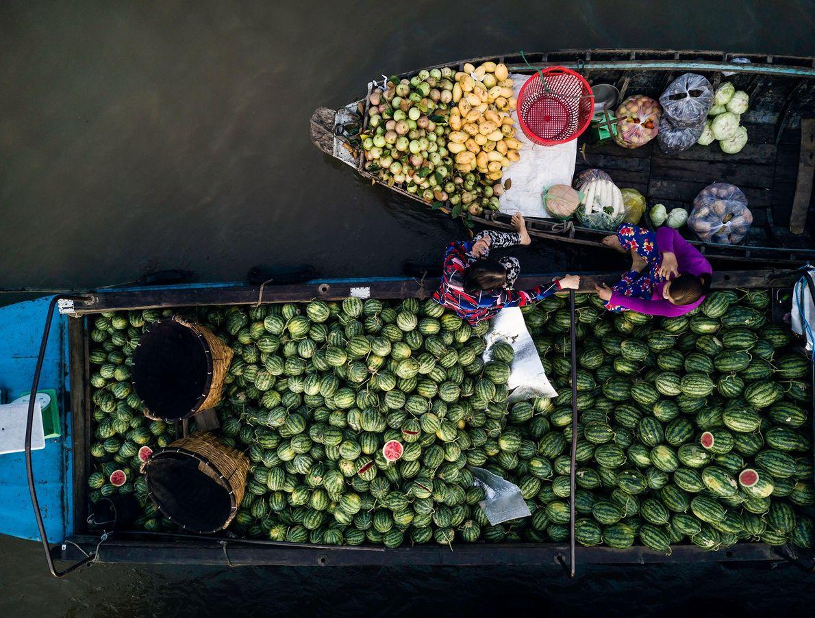 Fornecedores conversam enquanto aguardam clientes no mercado flutuante de Phong Dien, no Delta do Mekong.