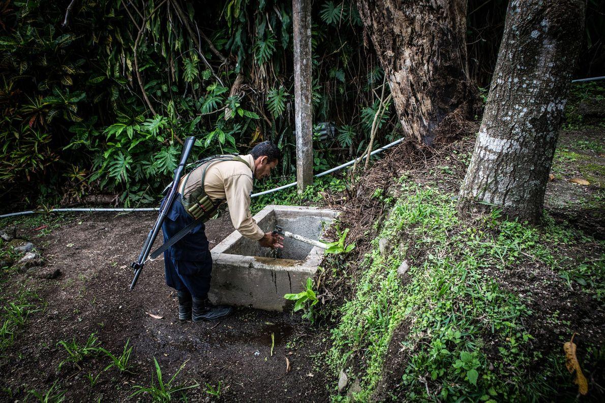 Um segurança lava as mãos em uma torneira ao ar livre no Miranda Cafe em Nejapa.