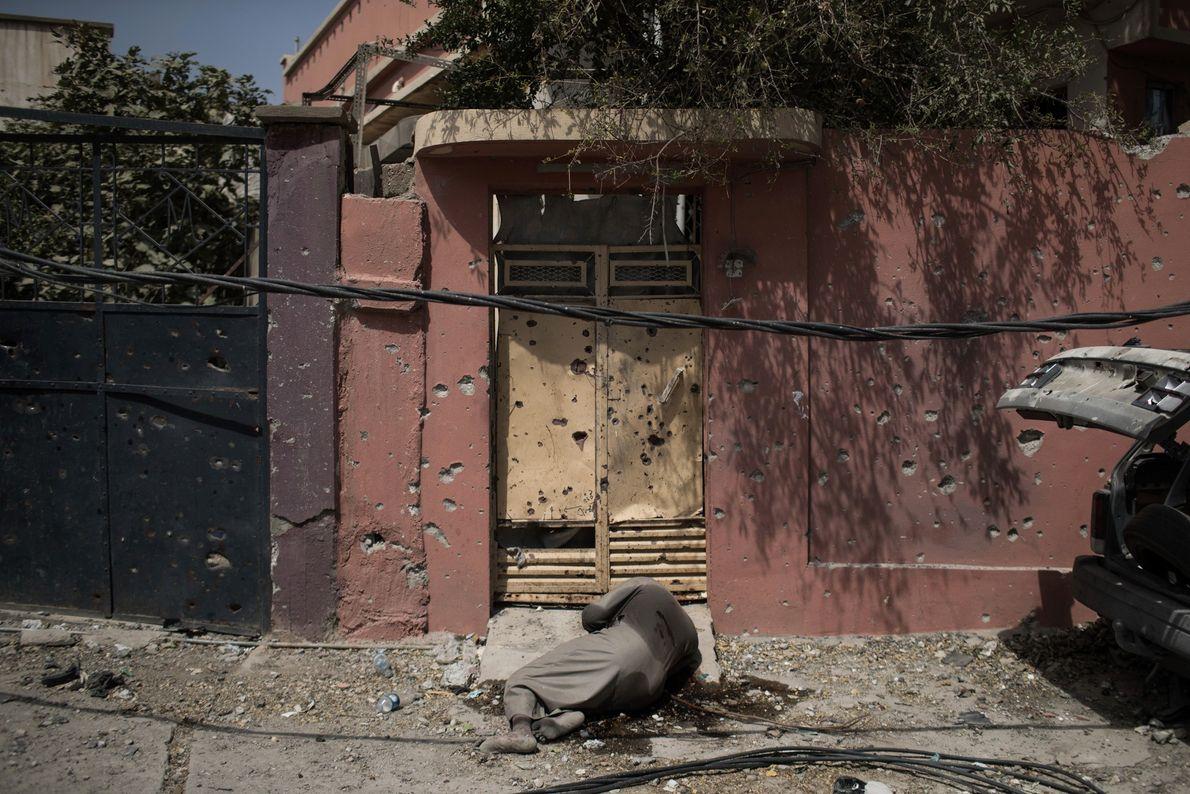 O corpo de um suposto militante do Estado Islâmico jaz na entrada de uma casa enquanto ...