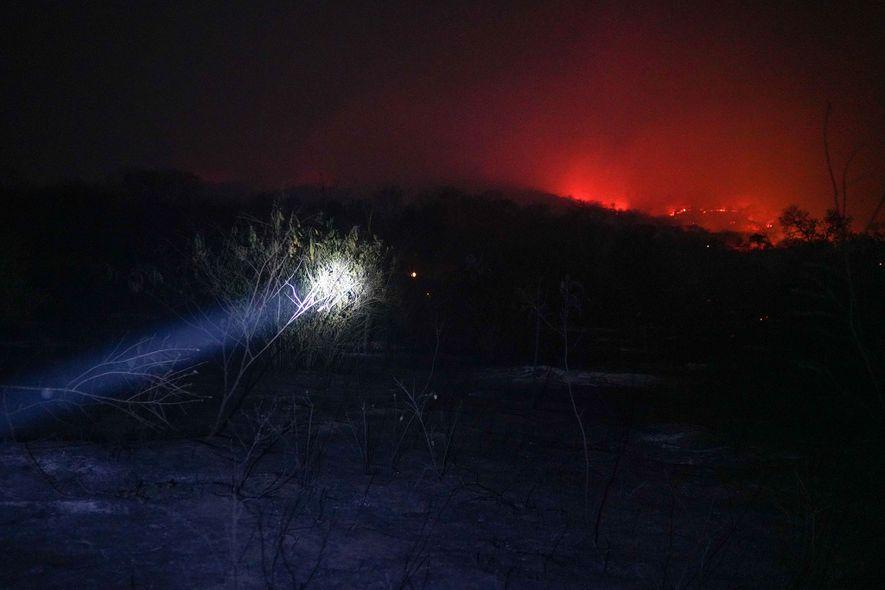 Bombeiros voluntários da comunidade de Roboré iluminam o caminho à medida que avançam em direção às ...