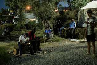 Residentes do acampamento improvisado, conhecido como Olival, se reúnem em áreas onde o sinal de celular ...