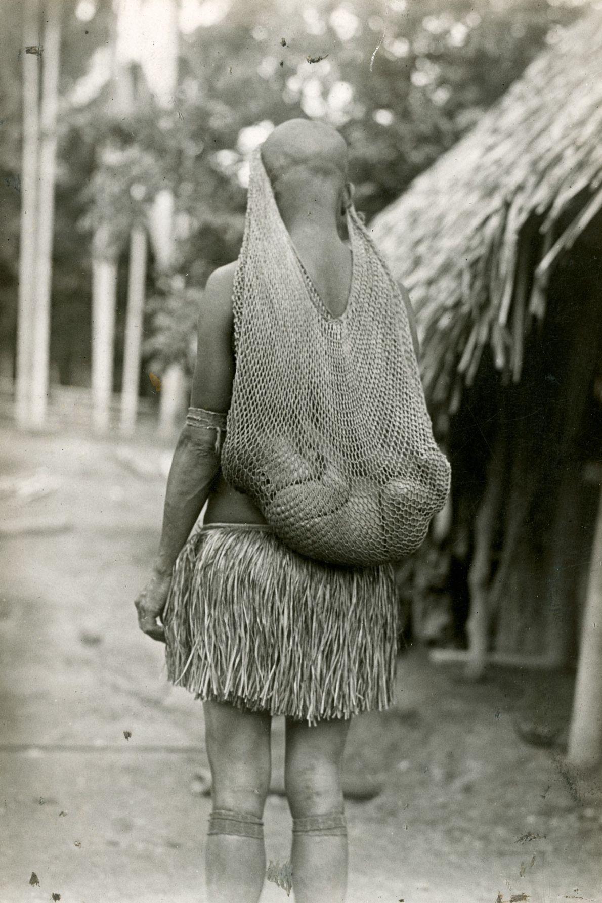 Um bebê dormindo em um berço de tecido na cabeça de sua mãe em Papua Nova ...