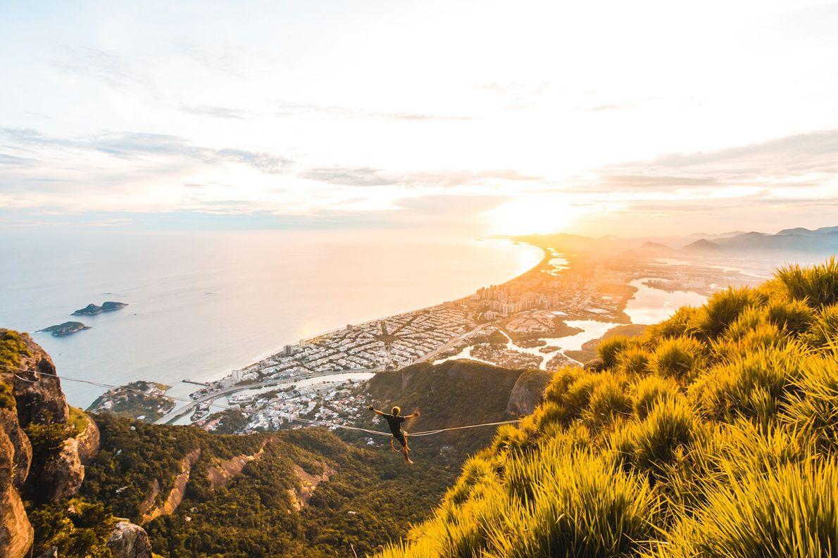 Praticante de high-line saúda o pôr do sol do alto da Pedra da Gávea, no Rio ...