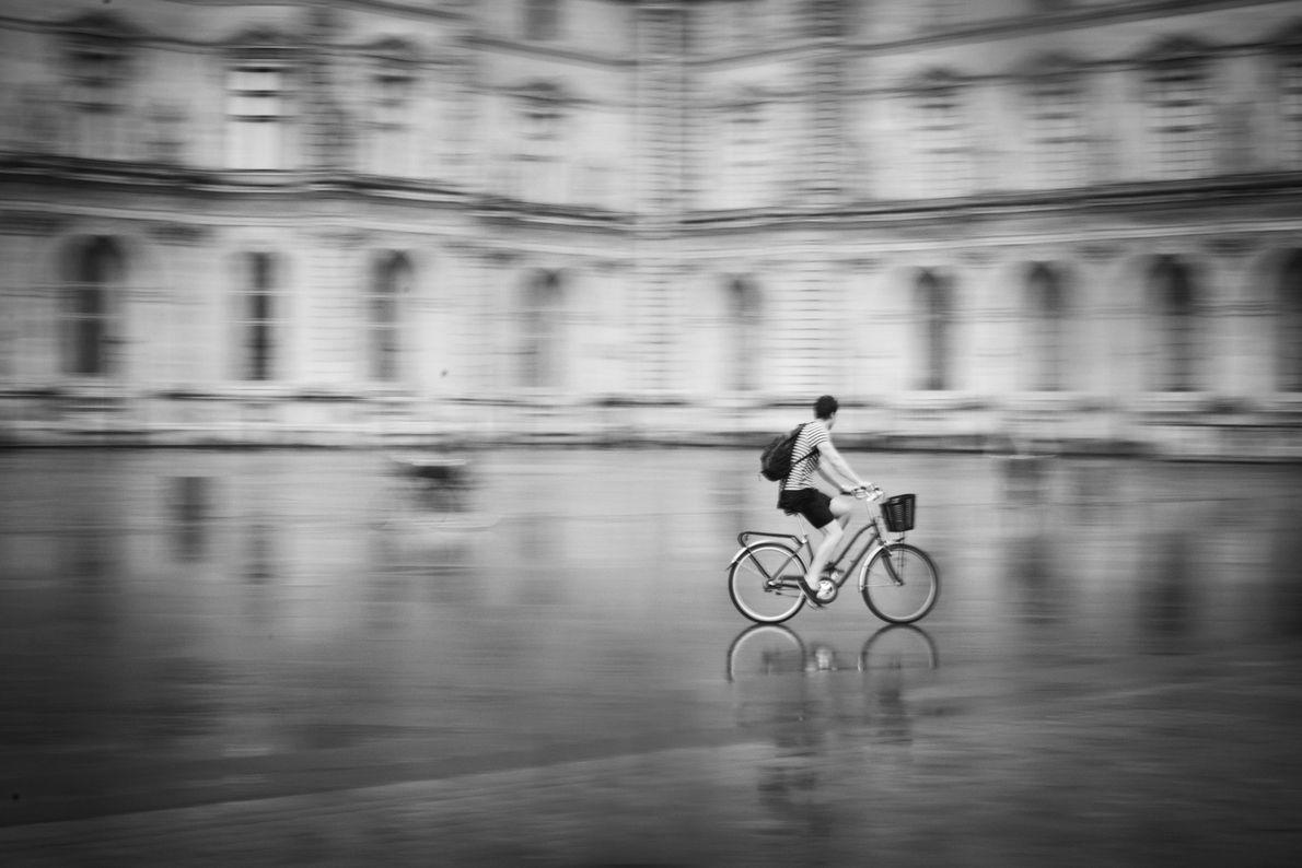 O estereótipo de parisienses andando de bicicleta pela cidade com uma baguete na cestinha da bicicleta ...