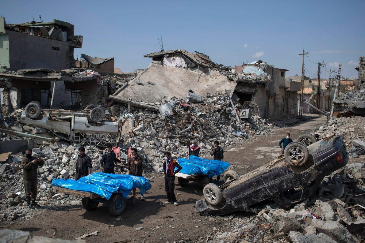 Residentes carregam corpos de várias pessoas mortas durante a batalha entre forças iraquianas e o Estado ...