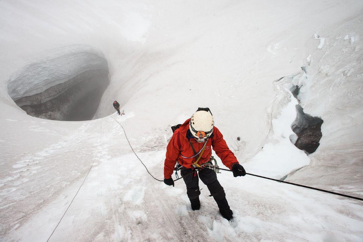 Neil Marchington, cientista e pesquisador, faz rapel em direção a Jared Smith, guia montanhista, e à ...