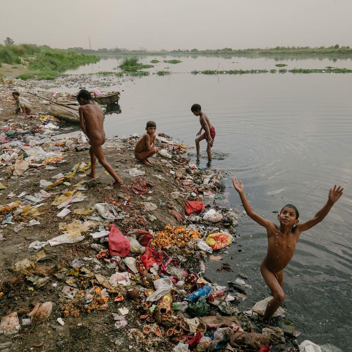 crianças brincam e trabalham em rio poluído