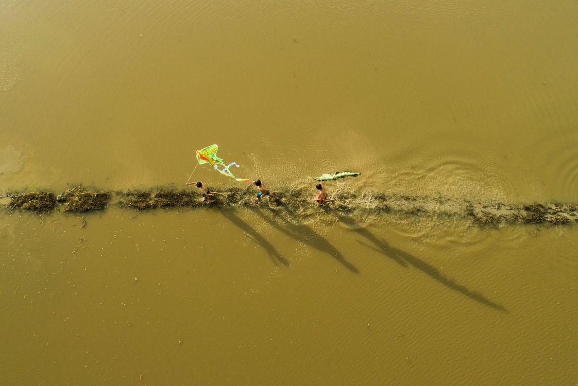 Crianças empinam pipas no Delta do Mekong durante a temporada anual de cheias.
