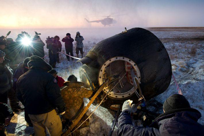 A equipe de apoio ajuda os passageiros da Soyuz TMA-02M—o astronauta Mike Fossum, da NASA, o ...