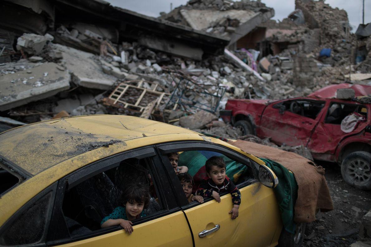 Crianças brincam em um carro destruído. A vizinhança foi liberada recentemente dos militantes do Estado Islâmico ...