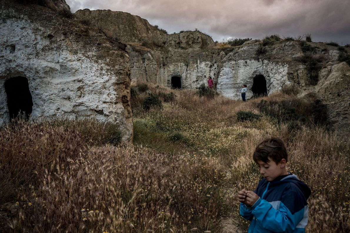 Crianças brincam em cavernas abandonadas vizinhas à caverna onde moram. No passado, todas as cavernas estiveram ...