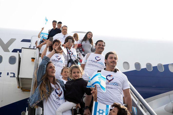Novos imigrantes desembarcam em meio a acaloradas boas-vindas.