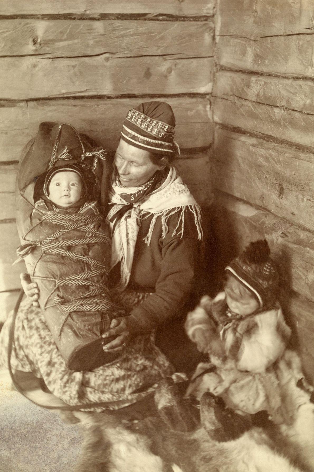 Uma mulher da Lapônia, bebê e criança na Lapônia, Finlândia, sentados nas peles que forram seu ...