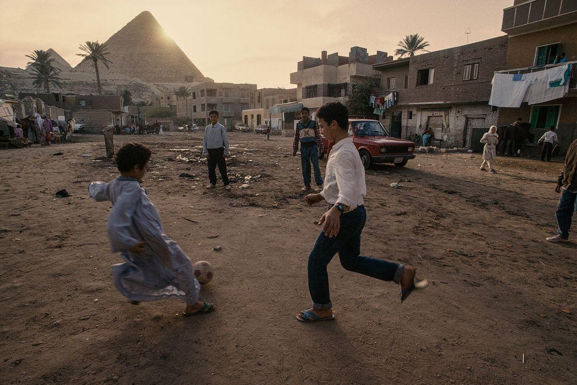 Crianças de um vilarejo jogam futebol aos pés das Pirâmides de Gizé no Egito.