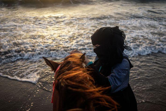 Mulher acalma cavalo, com o Mar Vermelho ao fundo, em Hodeida.
